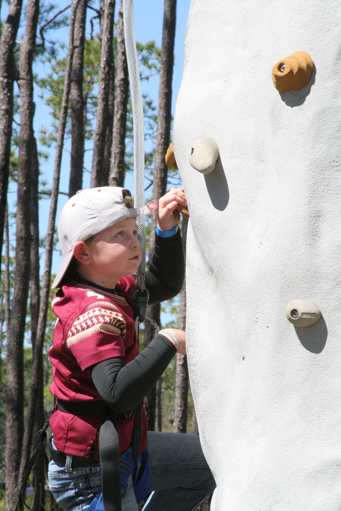 photo of a young boy rock wall climbing